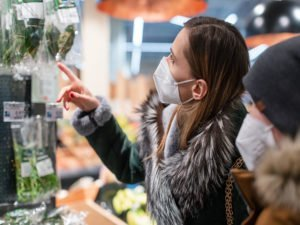 mutter und sohn tragen ffp2-masken beim einkauf